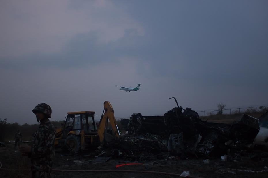 सोमबार काठमाडौंमा दुर्घटनामा परेको यूएस बंगलाको क्षतविक्षत अवस्थामा रहेको विमान । बंगलादेशबाट काठमाडौं आउँदै गरेको विमान अवतरणका क्रममा दुर्घटनामा परेको थियो । तस्बिर : सरिता खड्का