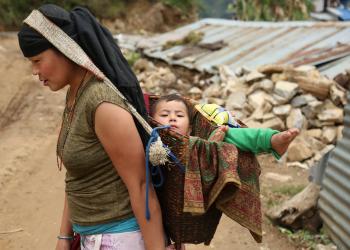 गोरखाको मान्द्रे गाउँमा कोक्रोमा बच्चा बोकेर काममा जाँदै स्थानीय महिला । तस्बिरः सरिता खड्का