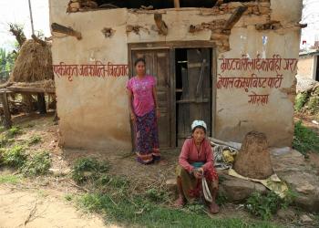 गोरखाको चोरकाटे टारमा भूकम्पले भत्किएको घरअघि थकाइ मार्दै स्थानीय महिला । तस्बिरः सरिता खड्का